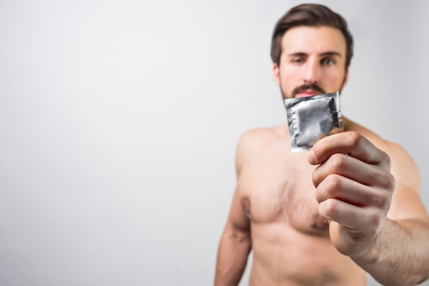 Handsome bearded man without a shirt, showing a condom. it's good to use it to prevent unexpected bad things with people. advertising concept. contraception. isolated on white wall