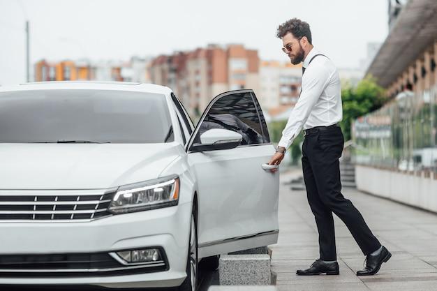 Красивый бородатый менеджер садится в машину, стоя на улице на улице города возле современного офисного центра