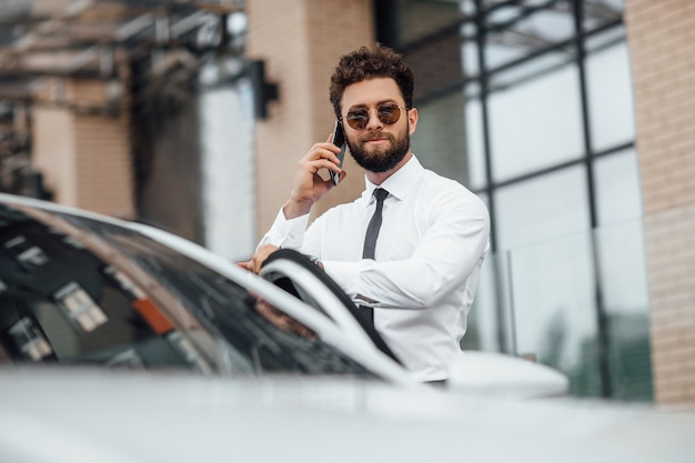 Handsome bearded manager in white shirt, speaking by phone and standing near his car outdoors on the streets of the city near the modern office center