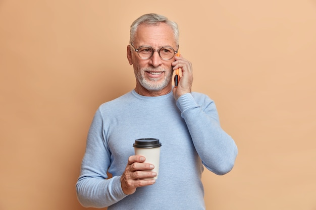 Handsome bearded mature man has telephone conversation with daughter during coffee break wears spectacles and blue jumper poses against beige wall