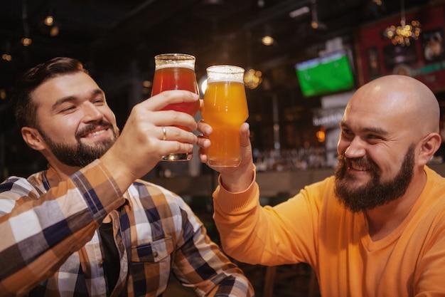 ビールのグラスをチリンとパブで祝うハンサムなひげを生やした男性