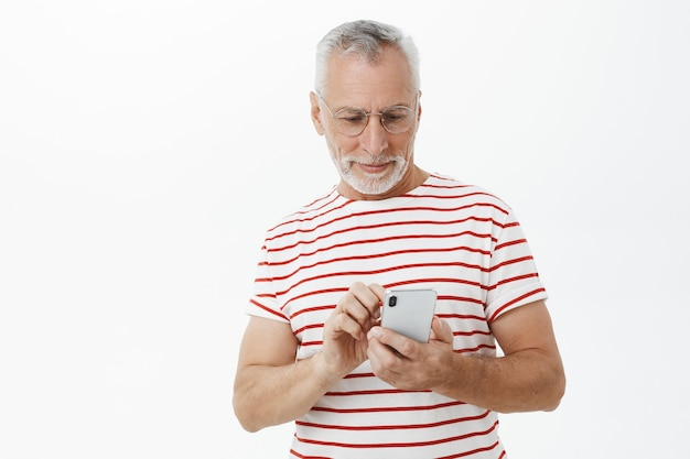 Handsome bearded old man using smartphone, texting message