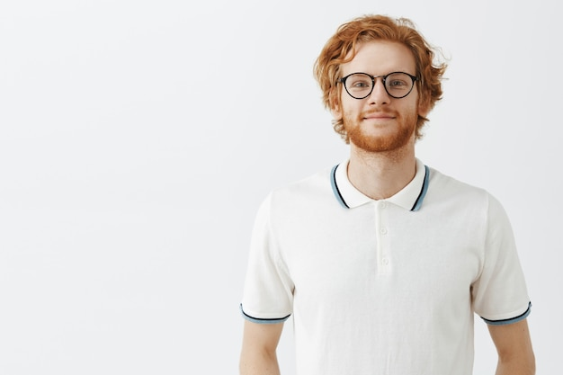 Handsome bearded redhead guy posing against the white wall with glasses