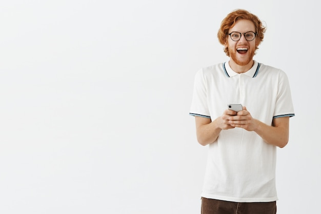 Handsome bearded redhead man using mobile phone