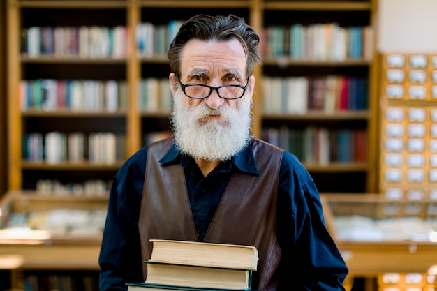 Handsome bearded senior academic professor or library worker, smiling and holding old books, while standing over the background of vintage library bookcases. knowledge concept
