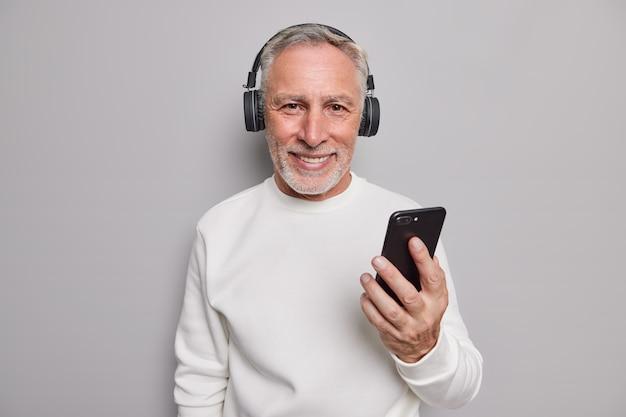 ハンサムなひげを生やした年配の男性の笑顔は、携帯電話とヘッドフォンを喜んで使用しています
