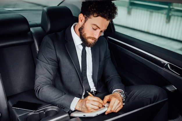 Handsome, bearded, smiling businessman working on the backseat of the car and makes notes in the notebook