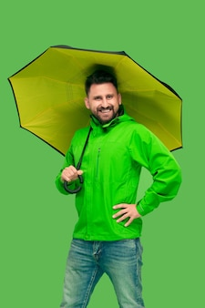 Handsome bearded smiling happy young man holding umbrella and looking at front isolated on vivid trendy green studio