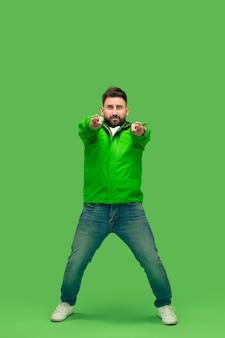 鮮やかなトレンディな緑のスタジオで隔離のカメラを見て、指しているハンサムなひげを生やした笑顔の幸せな若い男。