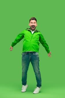 Красивый бородатый улыбающийся счастливый молодой человек, смотрящий вперед, изолированный на яркой модной зеленой студии