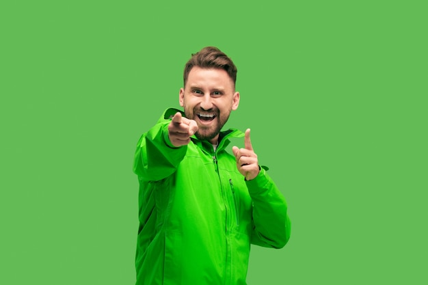 Handsome bearded smiling happy young man looking and pointing at camera isolated on vivid trendy green studio. concept of the autumn and cold time. human emotions concepts