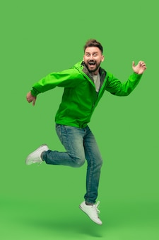 Handsome bearded smiling happy young man running isolated on vivid trendy green studio