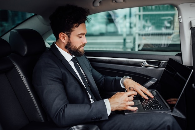 Handsome, bearded, smiling top manager in black suit working on his laptop on the backseat of the car