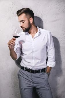 ハンサムなひげを生やしたソムリエの男は赤ワインを味わっています