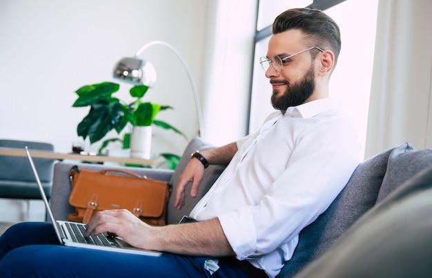 彼はラップトップで作業し、ソファに座っている間ハンサムなひげを生やしたスタイリッシュなビジネスマン