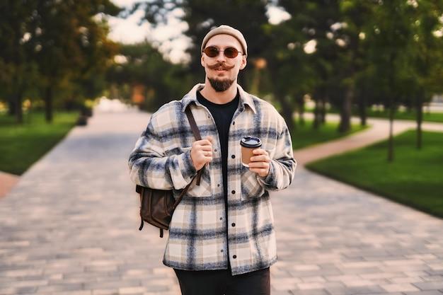 수염을 기른 멋진 힙스터는 휴식 시간을 가지면서 커피를 마시며 야외 공원을 산책합니다.