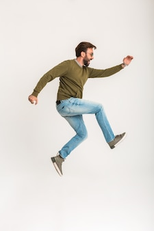 Handsome bearded stylish man jumping running isolated dressed in sweatshirt, wearing jeans and sunglasses