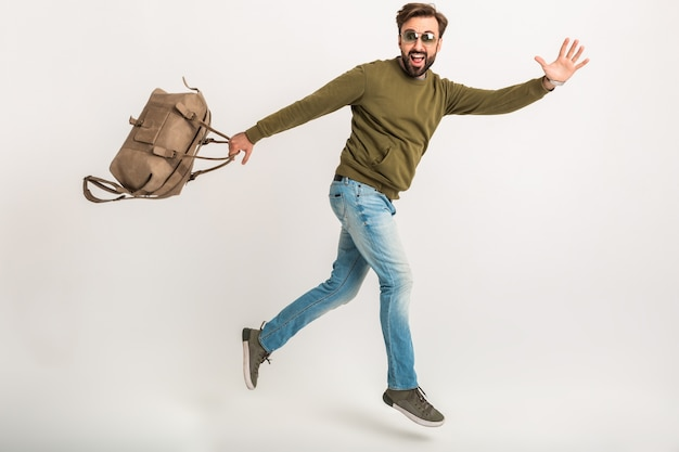 Handsome bearded stylish man jumping running isolated dressed in sweatshirt with travel bag, wearing jeans and sunglasses, crazy traveler on hurry