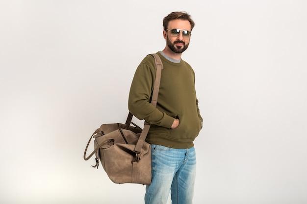 Красивый бородатый стильный мужчина позирует изолированно, одетый в толстовку с дорожной сумкой, в джинсах и солнцезащитных очках