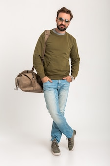 Handsome bearded stylish man posing isolated dressed in sweatshirt with travel bag, wearing jeans and sunglasses