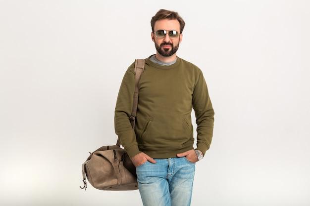 Uomo alla moda barbuto bello in posa isolato vestito di felpa con borsa da viaggio, jeans e occhiali da sole