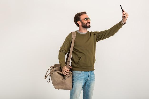 Uomo alla moda barbuto bello in felpa con borsa da viaggio, indossa jeans e occhiali da sole isolati prendendo selfie foto sul telefono
