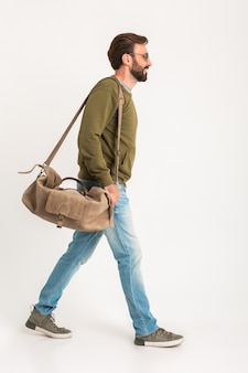 Handsome bearded stylish man walking isolated dressed in sweatshirt with travel bag, wearing jeans and sunglasses