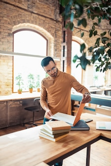 Handsome bearded writer. handsome bearded writer wearing glasses standing in light spacious printing office