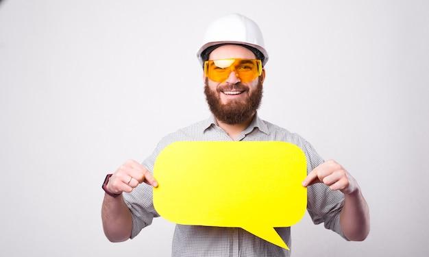 Красивый бородатый молодой архитектор в защитных очках и шлеме держит речевой пузырь и улыбается, смотрит в камеру возле белой стены