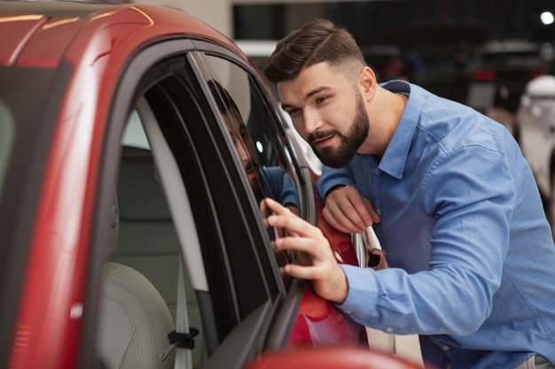 Handsome bearded young man examining new modern car at the dealership, copy space