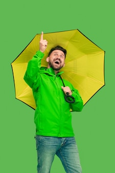 Handsome bearded young man holding umbrella