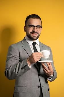 Красивый бородатый молодой человек в очках в формальной одежде держит чашку кофе на желтой стене