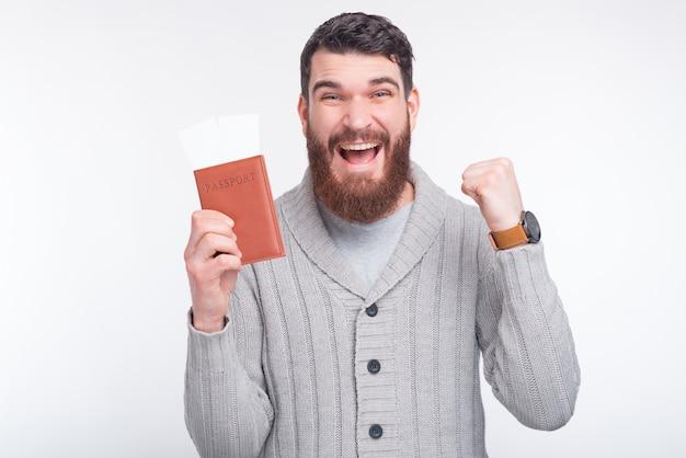 ハンサムなひげを生やした若い男は彼の財布を持っていると白い背景の近くのカメラに笑顔します。