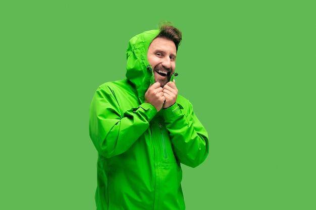 Bel giovane barbuto che guarda l'obbiettivo isolato sul verde