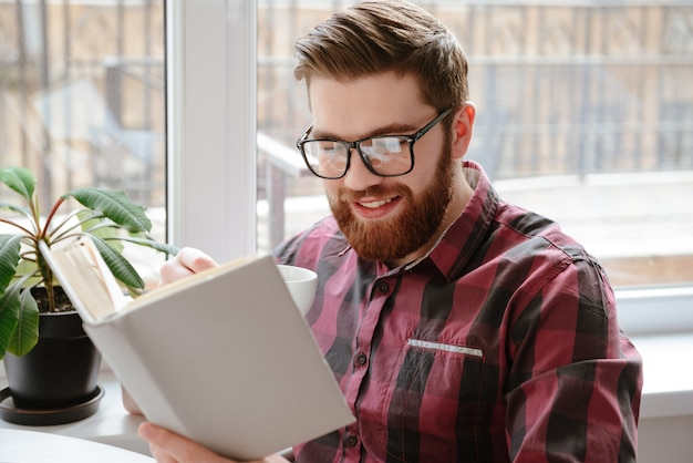 Handsome bearded young man reading books.