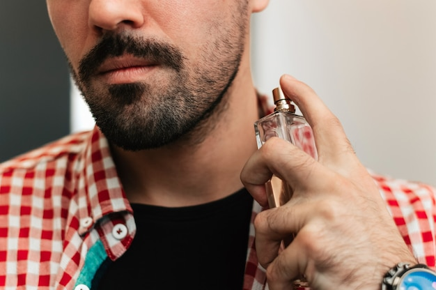 Handsome bearded young man spraying perfume.