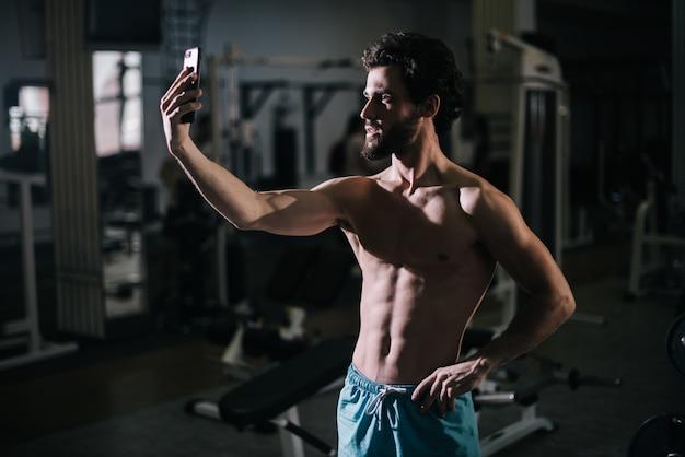스마트폰으로 셀카 사진을 찍는 근육질의 알몸 몸통을 가진 잘생긴 수염난 청년
