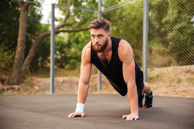 Красивый бородатый молодой спортсмен делает отжимания на открытом воздухе