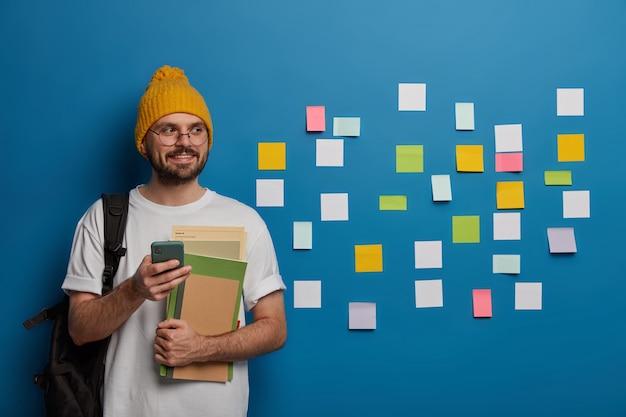 Красивый бородатый мальчик стоит с учебниками, мобильным телефоном и рюкзаком, отправляет текстовое сообщение однокласснику Бесплатные Фотографии