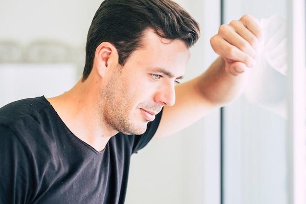 Красивый красивый голубые глаза кавказец черные волосы модель мужчина смотрит в окно погруженный в свои мысли