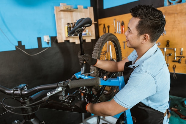 안장을 설치할 때 장갑을 끼고 앞치마를 입은 잘생긴 자전거 정비사