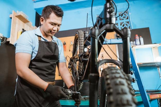 자전거 페달을 설치할 때 장갑을 끼고 앞치마를 입은 잘생긴 자전거 정비사