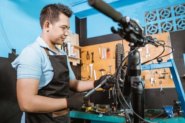 충격 흡수 장치를 조정하기 위해 고압 자전거 펌프를 사용하는 잘 생긴 자전거 정비사