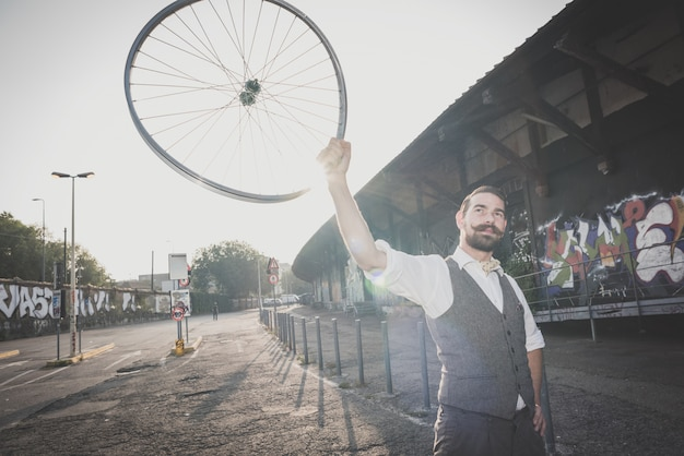 Handsome big moustache hipster man holding old bicycle wheel