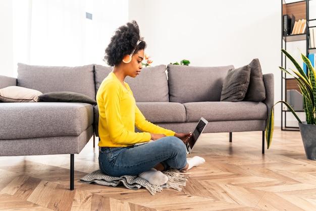집에서 컴퓨터 노트북과 헤드폰으로 음악을 듣고 있는 잘생긴 흑인 성인 여성 - 집에서 원격 온라인으로 일하는 예쁜 흑인 소녀