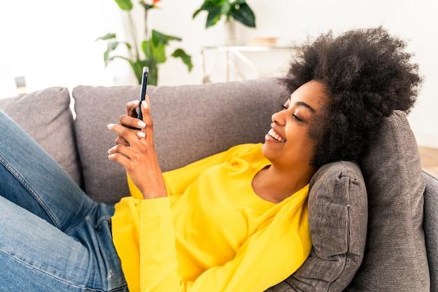 스마트폰으로 소셜 네트워크 앱에서 온라인 비디오를 보고 있는 집에서 잘생긴 흑인 성인 여성 - 휴대폰으로 원격 온라인에서 일하는 예쁜 흑인 소녀