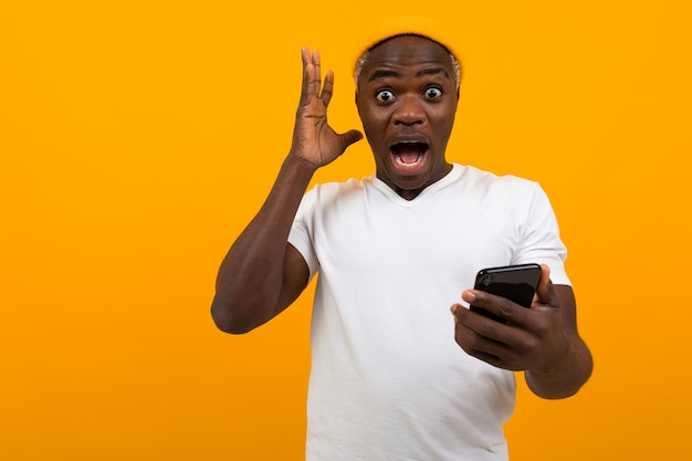 Handsome black african man looks in surprise on the phone on yellow