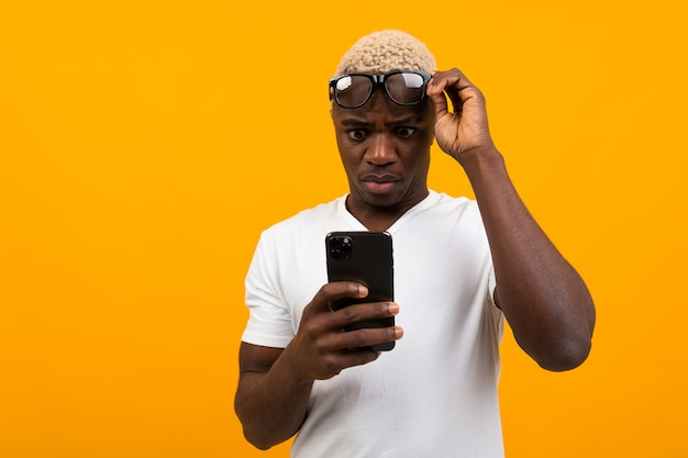 Handsome black african man looks in surprise on the phone on a yellow