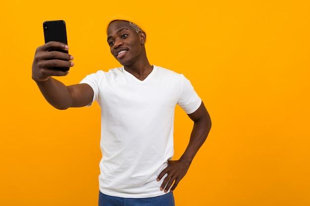 ハンサムな黒人アフリカ人がコピースペースとオレンジ色の電話でselfieを作る