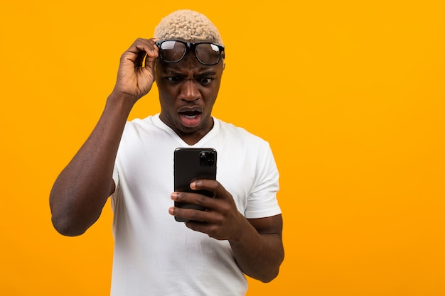 Handsome black african man with glasses looks in surprise on the phone on yellow with copy space
